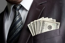 Businessman with money in suit pocket