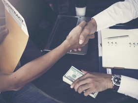 Man offering batch of hundred dollar bills. Hands close up. Vena