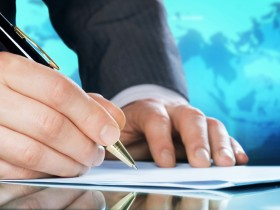 Businessman's hand with a pen. International business concept