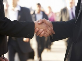 Businessman and business woman shaking hands in street