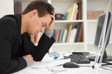 Stressed young man at home desk
