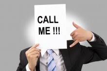 businessman holding call me billboard