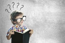 Child with a book looking for answers