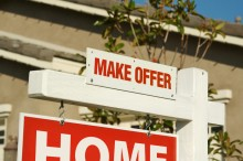 Make Offer Real Estate Sign in Front of Beautiful New Home.