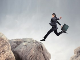 Businessman jumping from a rock to another