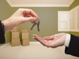Woman Handing Over the House Keys To A New Home Inside Empty Green Colored Room.