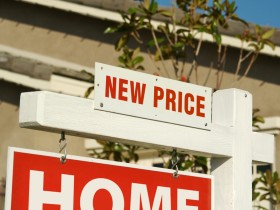 New Price Real Estate Sign in Front of Beautiful New Home.
