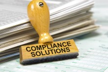 compliance solutions marked on rubber stamp