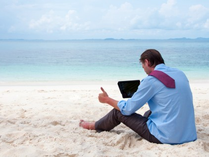 Business man sitting and working on the beach with tablet comput