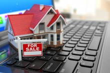 Real estate agency online. House on laptop keyboard.
