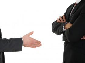 Person Offering Handshake To Businessman With Arm Crossed