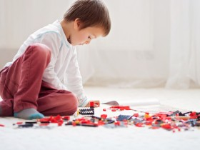 Little child playing with lots of colorful plastic blocks indoor