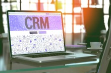 CRM on Laptop in Modern Workplace Background.