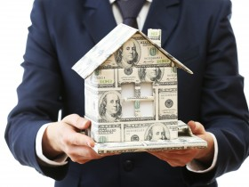 Model of house made of money in male hands isolated
