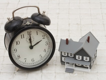 Time to buy a house, A gray house and alarm clock on stone backg