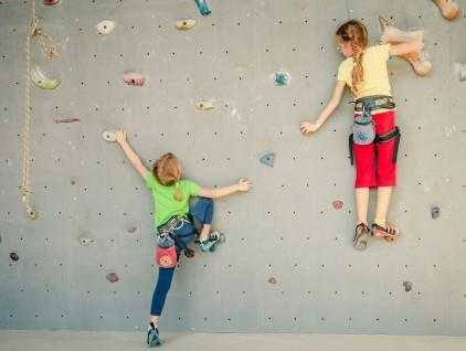 two little girls climbing a rock wall