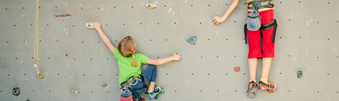 two little girls climbing a rock wall